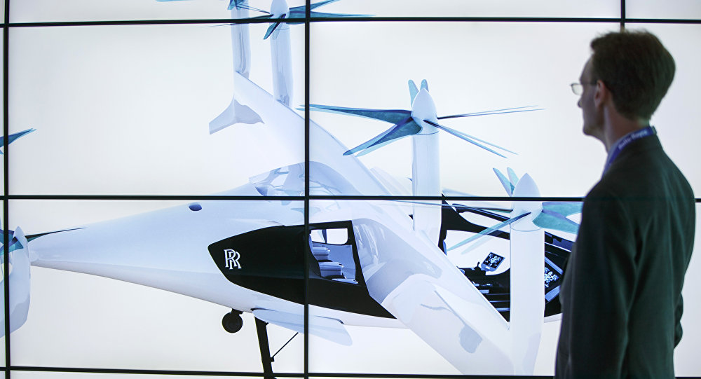 A man poses alongside screens presenting the Rolls-Royce EVTOL air taxi concept during the Farnborough Airshow, south west of London, on July 16, 2018