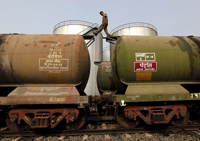 A worker walks atop a tanker wagon to check the freight level at an oil terminal on the outskirts of Kolkata, India November 27, 2013