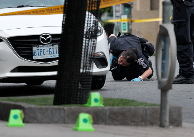 A police officer looks for evidence under a car while investigating a mass shooting on Danforth Avenue in Toronto, Canada, July 23, 2018.