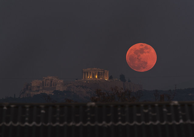 A boat sails in the Bosporus Strait separating Europe and Asia, as a super blue blood moon rises over Istanbul, Wednesday, Jan. 31, 2018. It's the first time in 35 years a blue moon has synced up with a supermoon and a total lunar eclipse, or blood moon because of its red hue, all rolled into one celestial phenomenon