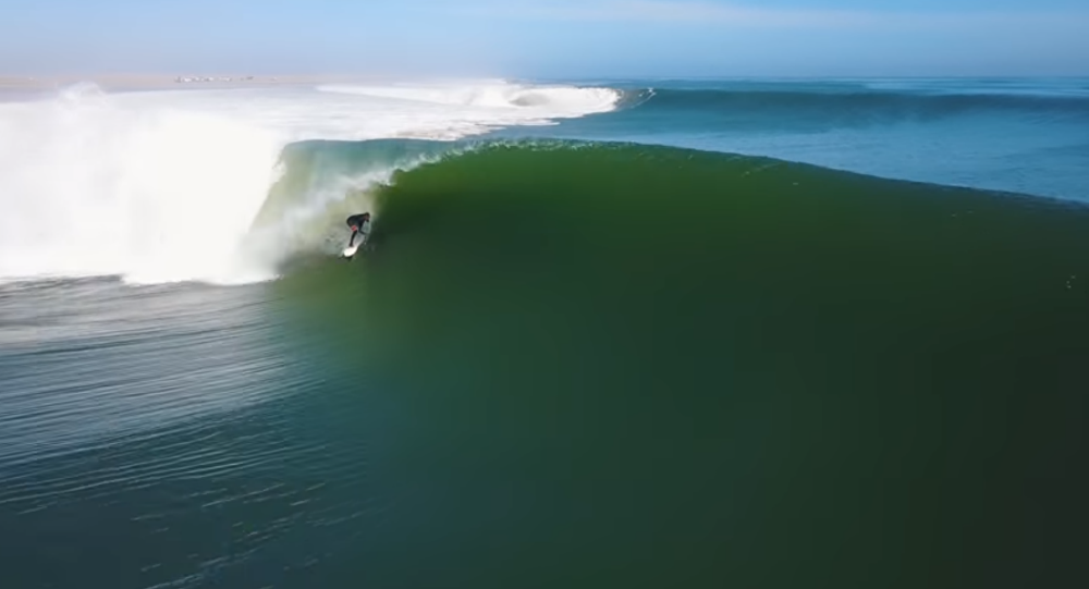 Surfer Koa Smith creates magic by riding Namibian wave for two minutes, conquering eight barrels.