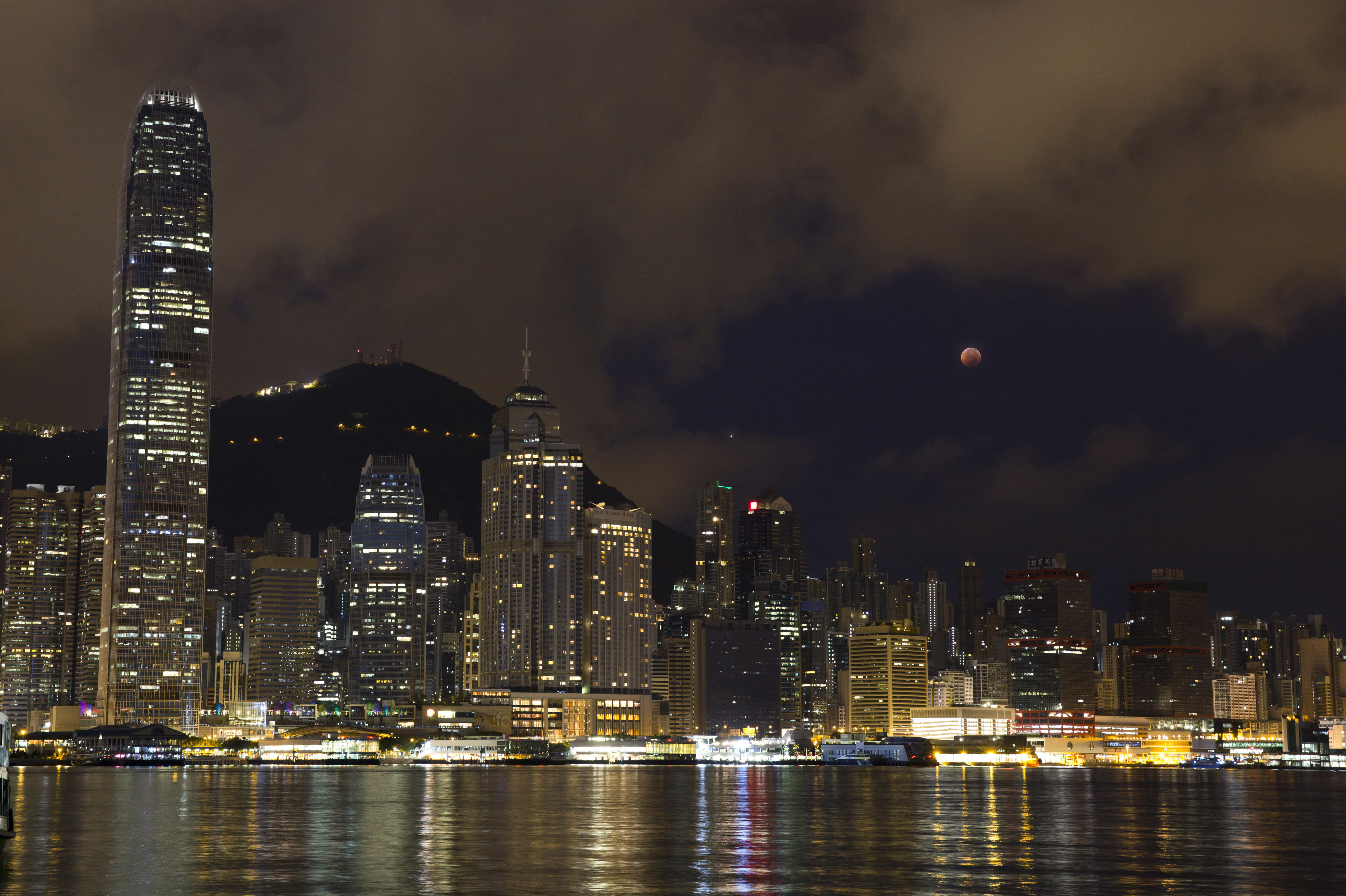 A full moon rises over the Victoria Harbour during a complete lunar eclipse, in Hong Kong, Saturday, July 28, 2018. Skywatchers around much of the world are looking forward to a complete lunar eclipse that will be the longest this century.