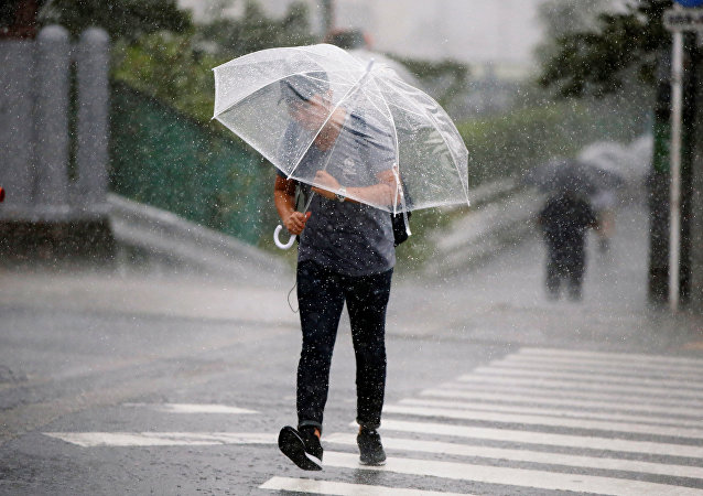 Passersby using umbrella struggles against a heavy rain and wind as Typhoon Jongdari approaches Japan's mainland in Tokyo, Japan July 28, 2018.