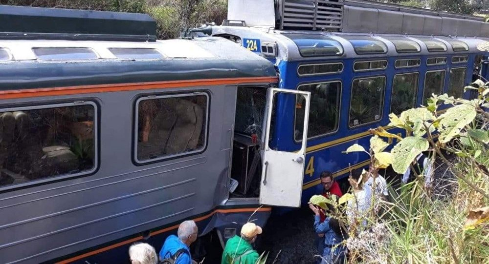In this photo provided by the government news agency Andina, passeners observe two trains after they collided in Cuzco, Peru, Tuesday, July 31, 2018