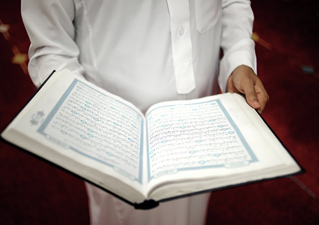 An imam holds the Quran after a prayer at a mosque