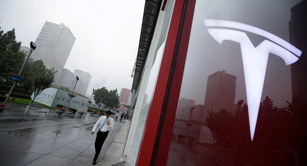 A man walks near a logo of Tesla outside its China headquarters at China Central Mall in Beijing, China July 11, 2018