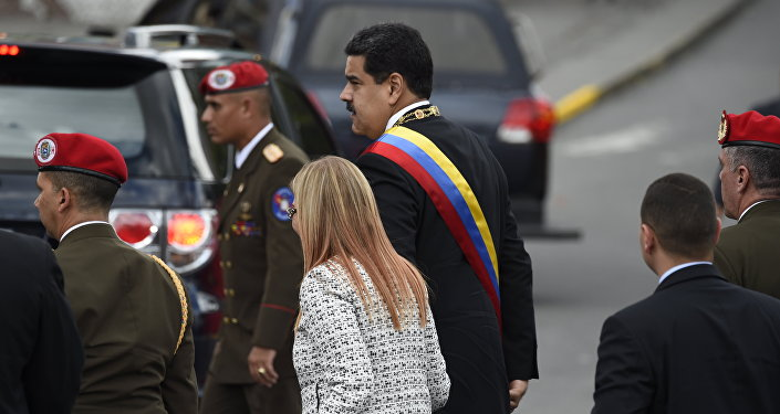 Venezuelan President Nicolas Maduro (C) and his wife Cilia Flores arrive for a ceremony to celebrate the 81st anniversary of the National Guard in Caracas on August 4, 2018 day in which Venezuela's controversial Constituent Assembly marks its first anniversary. The Constituent Assembly marks its first anniversary on August 4 as the embodiment of Maduro's entrenchment in power despite an economic crisis that has crippled the country's public services and destroyed its currency. The assembly's very creation last year was largely responsible for four months of street protests that left some 125 people dead.