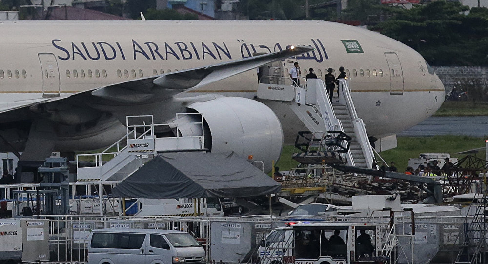 Security stand on the stairs of the Saudi Arabian Airlines plane Flight SV872 from Jiddah as it stays at an isolated area at Manila's International Airport in Pasay, south of Manila, Philippines on Tuesday, Sept. 20, 2016