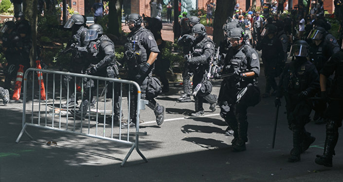 Police move in on protesters during a rally in Portland, Ore., Saturday, Aug. 4, 2018.