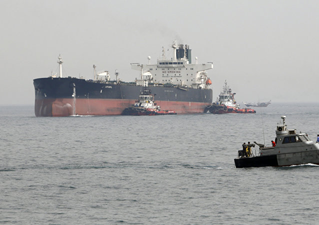 A picture taken on March 12, 2017, shows an Iranian military speedboat patrols the waters as a tanker perpares to dock at the oil facility in the Khark Island, on the shore of the Gulf