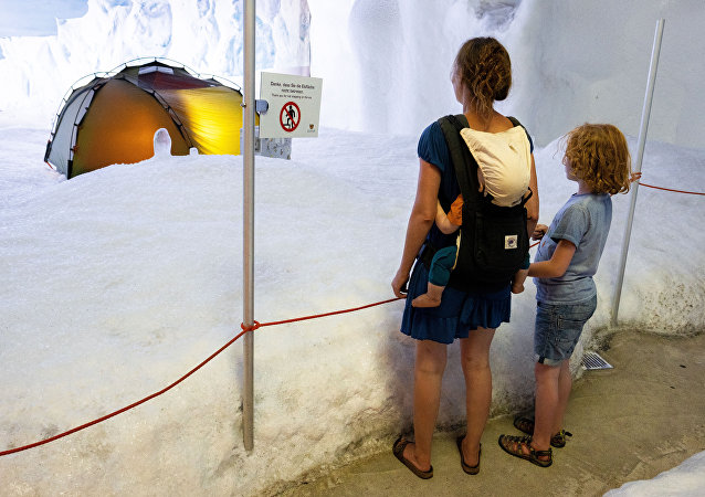 A woman and a child look at the antarctic exhibition at minus 6 degree in the climate exhibition center Climate house in Bremerhaven, northern Germany, on August 3, 2018 as a heatwave sweeps across northern Europe
