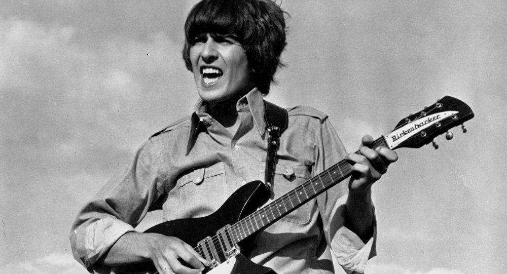 Beatle George Harrison is shown playing the guitar in a scene from the Beatles movie Help! on location in the Bahamas in 1965.