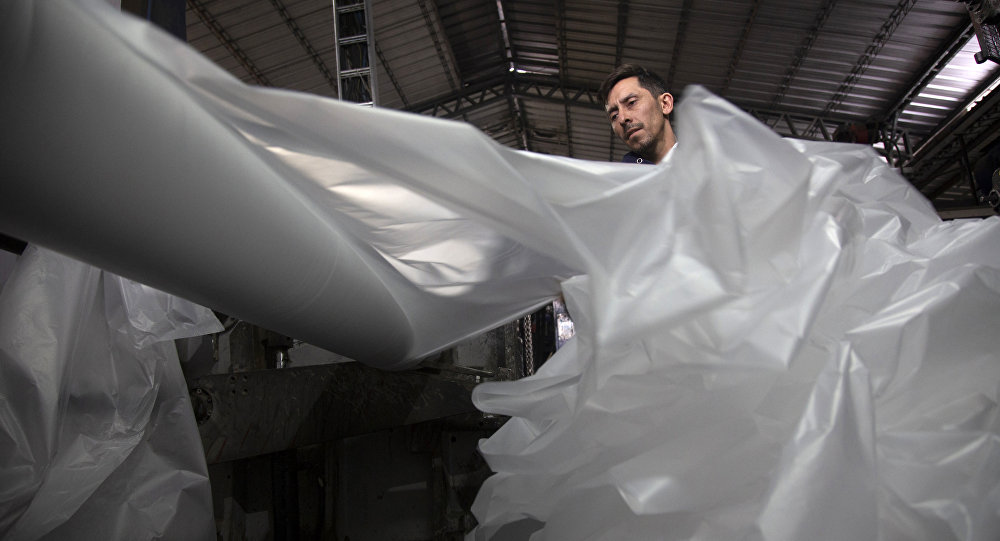 A worker checks the printing of supermarket plastic bags in a factory in Santiago, on July 18, 2018.