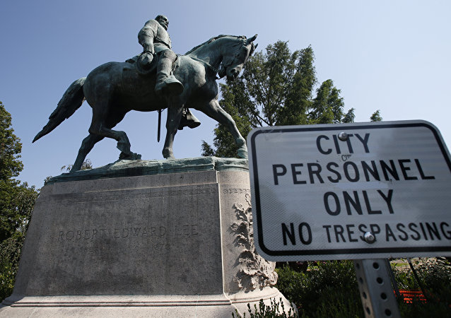 In this Monday, Aug. 6, 2018 photo, a No Trespassing sign is displayed in front of a statue of Robert E. Lee in Charlottesville, Va., at the park that was the focus of the Unite the Right rally. Pressure to take down America's monuments honoring slain Confederate soldiers and the generals who led them didn't start with Charlottesville. But the deadly violence that rocked the Virginia college town a year ago gave the issue an explosive momentum.