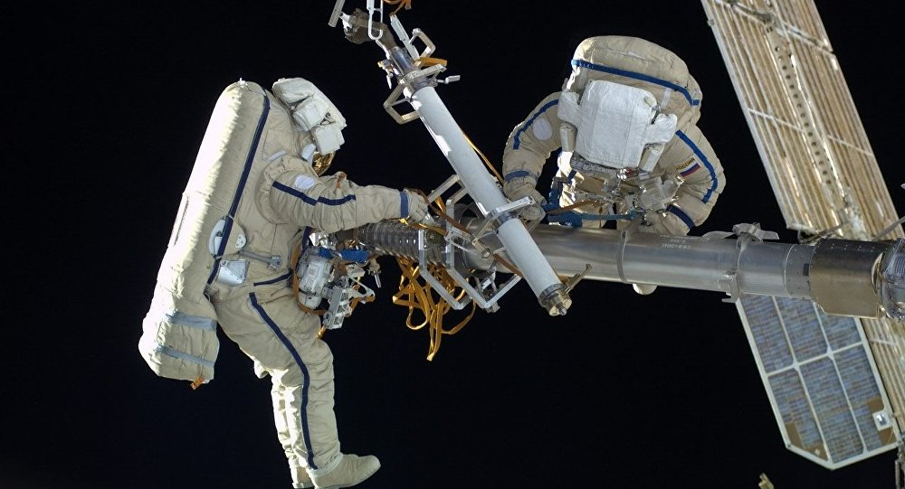 Two Russian cosmonauts, wearing  space suits, Orlan-MK