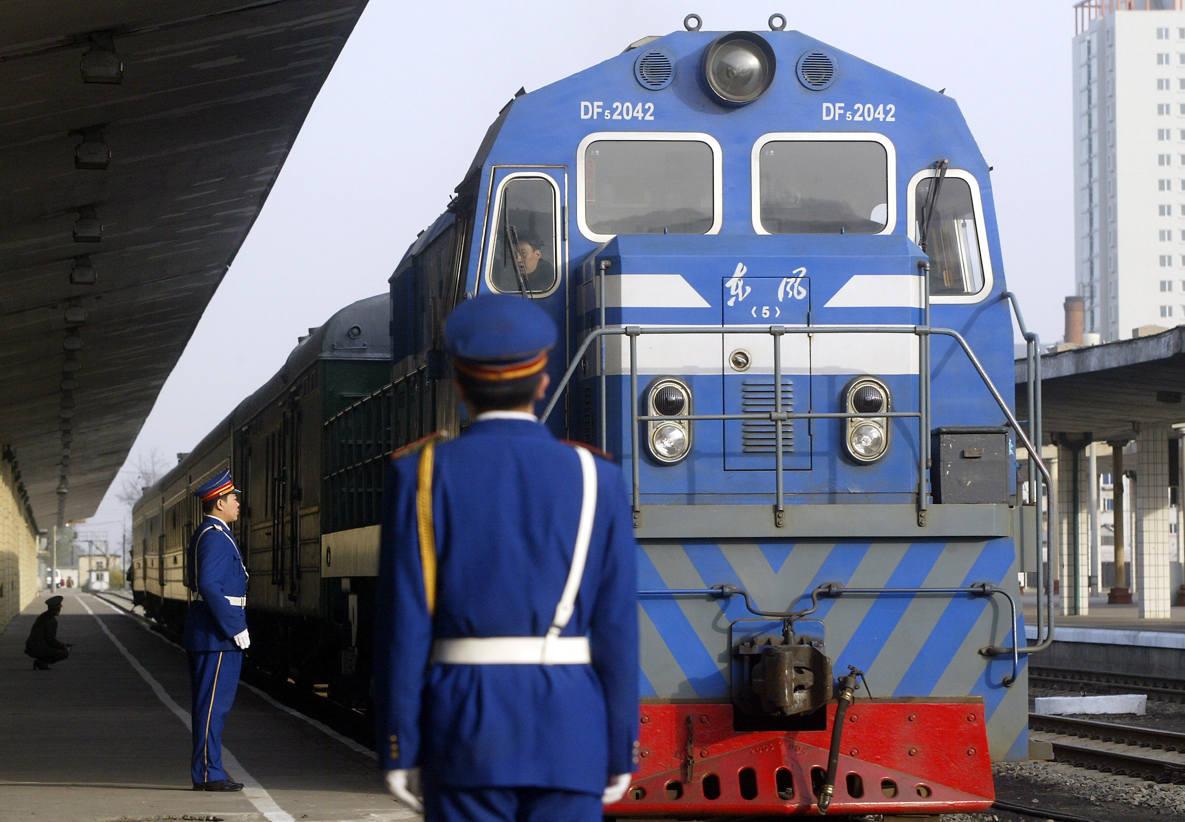 In this file photo, Chinese railway police stand on the platform as a passenger train from North Korea pulls into Dandong station