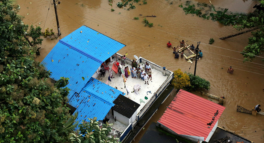 People wait for aid on the roof of their house at a flooded area in the southern state of Kerala, India, August 17, 2018