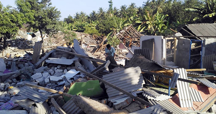A man inspects destroyed homes following an earthquake on Lombok island, Indonesia, Monday, Aug. 20, 2018. Multiple strong earthquakes killed a number of people on the Indonesian islands of Lombok and Sumbawa as the region was trying to recover from a temblor earlier this month that killed hundreds of people