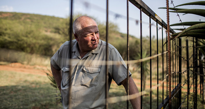 Piet Swanepoel looks through the boundary fence at his guest lodge on a farm in Limpopo province, South Africa, on October 31, 2017
