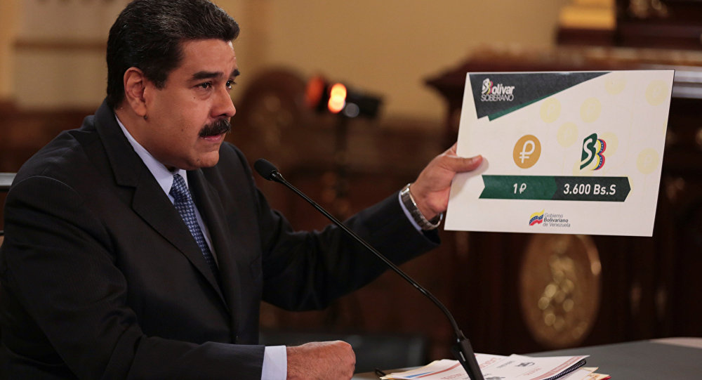 Venezuela's President Nicolas Maduro holds a sign showing the value of a Petro compared with the new Venezuelan currency Bolivar Soberano (Sovereign Bolivar), as he speaks during a meeting with ministers at Miraflores Palace in Caracas, Venezuela August 17, 2018.