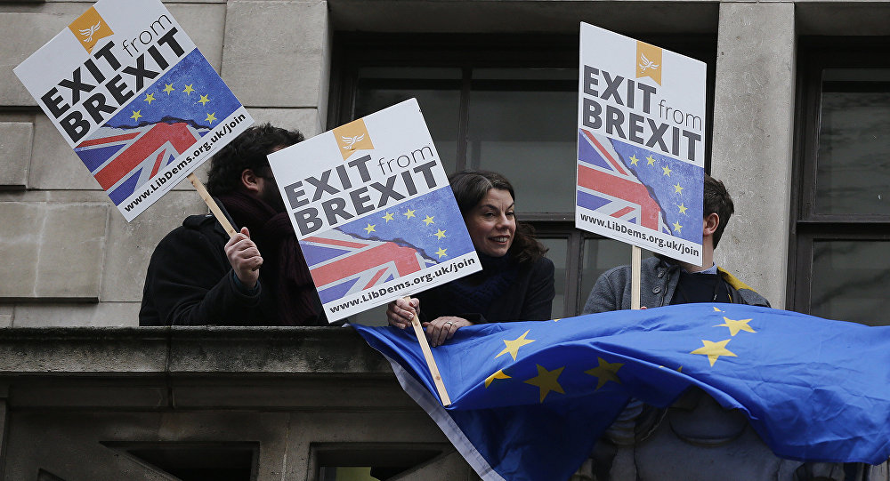 People demonstrate against Brexit on a balcony in London, Wednesday, Feb. 14, 2018, as Britain's Foreign Secretary Boris Johnson delivers a speech focusing on Britain leaving the EU. The Foreign Office says Johnson will use a speech Wednesday to argue for an outward-facing, liberal and global Britain after the U.K. leaves the bloc