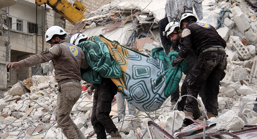 Syrian civil defence volunteers, known as the White Helmets, carry a body retrieved from the rubble following reported government airstrike on the Syrian town of Ariha, in the northwestern province of Idlib, on February 27, 2017