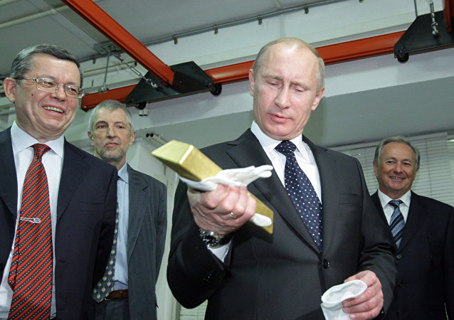 January 24, 2011. Russian Prime Minister Vladimir Putin holding a gold bar while visiting the Central Depository of the Bank of Russia. Georgy Luntovsky (left), first deputy chief of the Central Bank of Russia