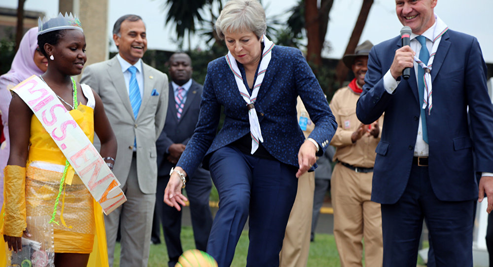Britain's Prime Minister Theresa May kicks a ball made of recycled plastic as former Norwegian politician and Executive Director of the UN Environment Programme Erik Solheim looks on during her visit to the United Nations complex within Gigiri in Nairobi, Kenya August 30, 2018.