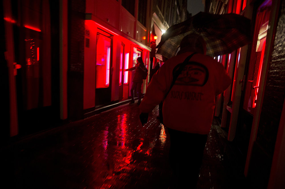 People walk through a narrow alley in the Red Light district in Amsterdam, Netherlands, Friday, Dec. 8, 2017. Every weekend, the heart of the historic port city, with its strip joints, seedy bars and scantily-clad prostitutes flaunting themselves behind plate glass windows, is overrun by foreign visitors over for stag and hen nights or to smoke marijuana in one of the city's many coffee shops.