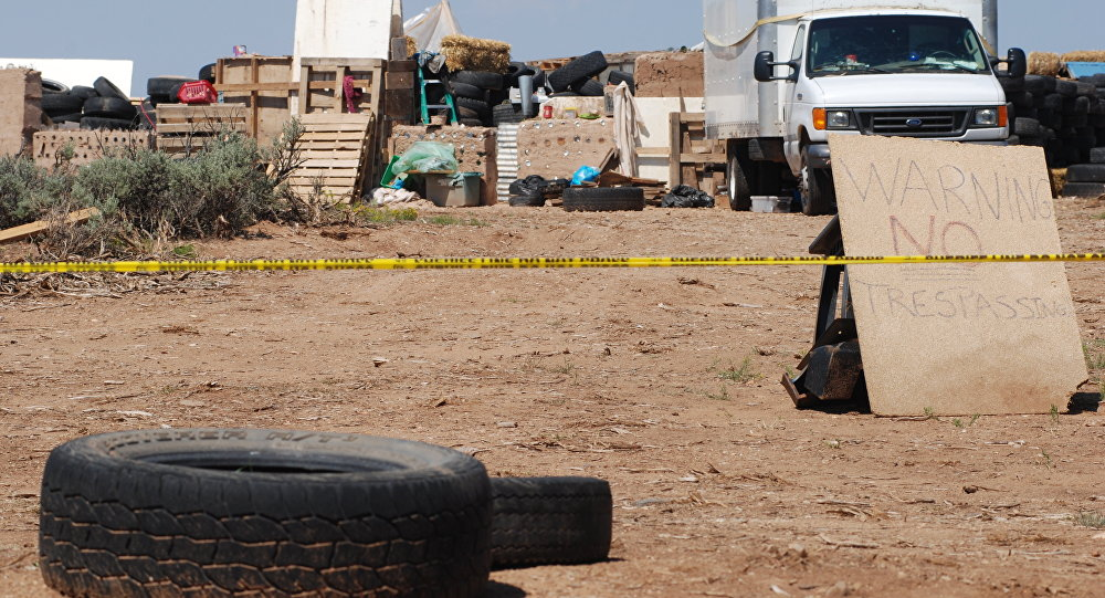 Police tape restricts access to a disheveled living compound in Amalia, N.M., on Tuesday, Aug. 7, 2018.