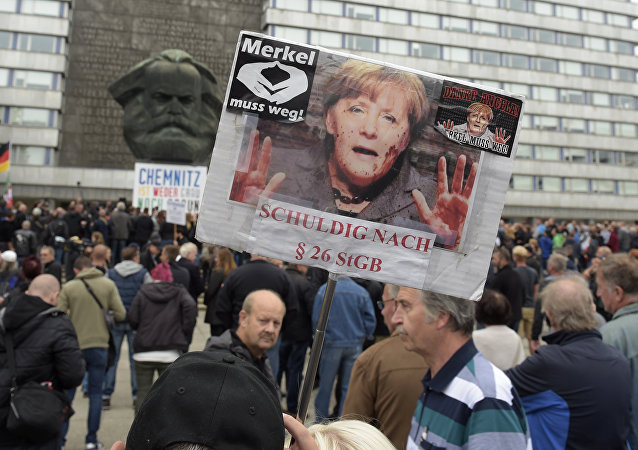 A protestor holds a poster with a photo of Angela Merkel reading 'Merkel must go and referring she is guilty of incitement in Chemnitz, eastern Germany, Saturday, Sept. 1, 2018, after several nationalist groups called for marches protesting the killing of a German man last week, allegedly by migrants from Syria and Iraq