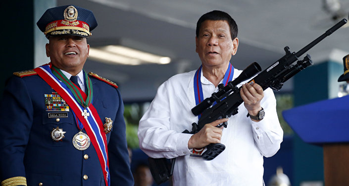 Philippine President Rodrigo Duterte, right, holds an Israeli-made Galil rifle which was presented to him by former Philippine National Police Chief Director General Ronald Bato Dela Rosa. File photo