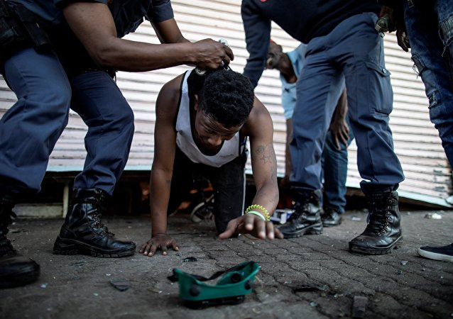 A suspected looter is detained by South African police officers as he emerges from of a looted foreign-owned shop in Soweto, Johannesburg, on August 29, 2018 during unrest that erupted after a foreign shop owner allegedly shot and killed a member of the community during a demonstration