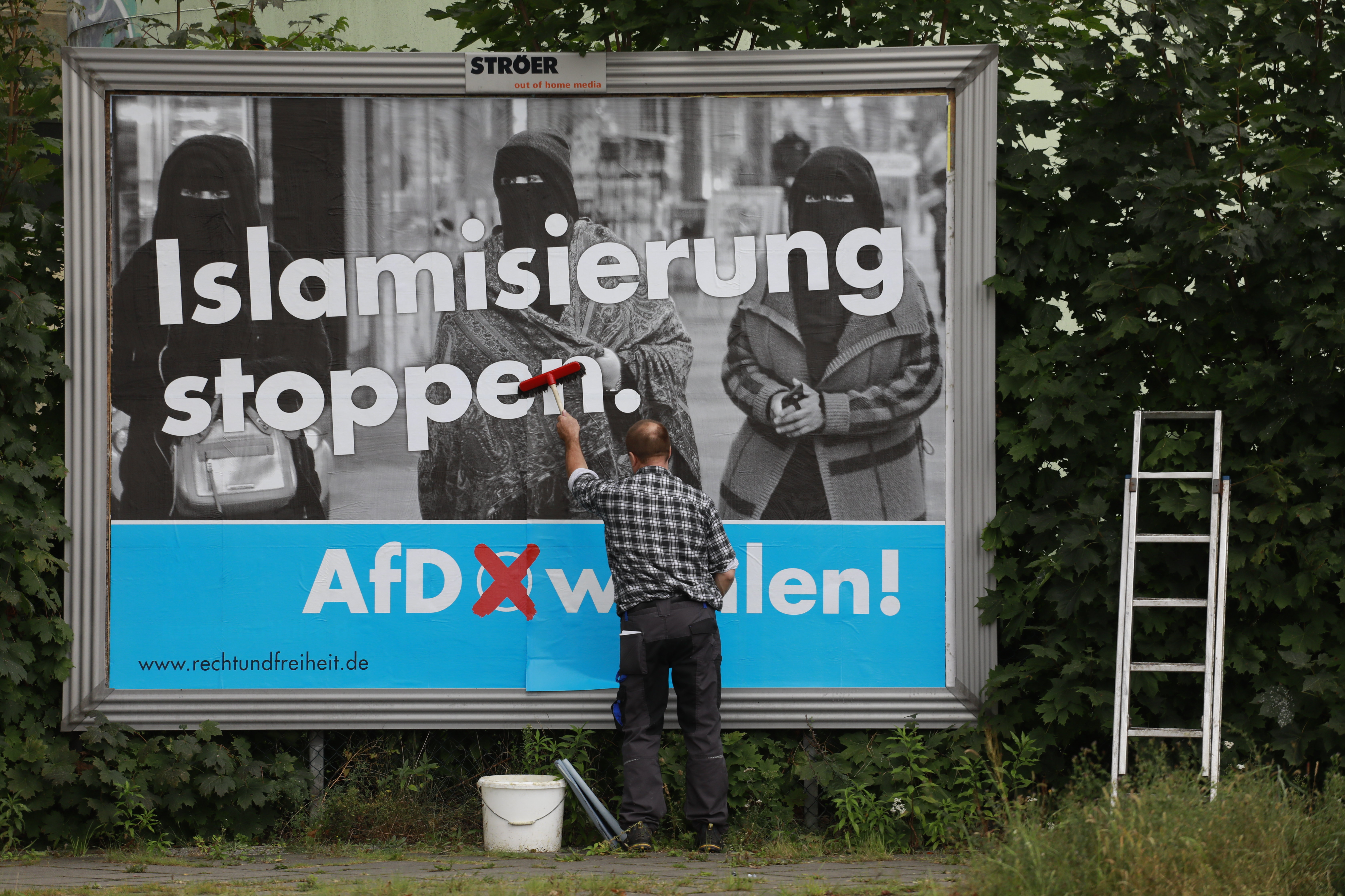 A man sticks an Alternative for Germany (AfD)'s electoral poster reading stop islamization in Berlin on September 7, 2017