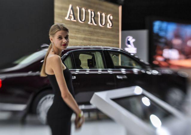 A girl posing at the Aurus Senat car at the Moscow International Motor Show 2018.