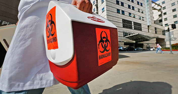 A research assistant with the David Geffen School of Medicine at UCLA carries a portable cooler marked with a biohazard label past the Ronald Reagan UCLA Medical Center in Los Angeles, Thursday, Feb. 19, 2015