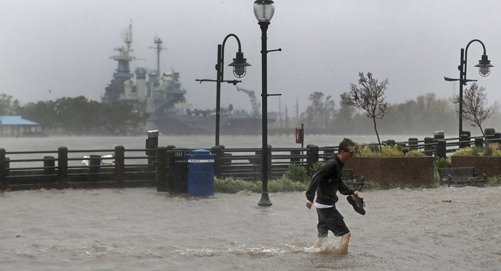 A man crosses a flooded street in downtown Wilmington, N.C., after Hurricane Florence made landfall Friday, Sept. 14, 2018.