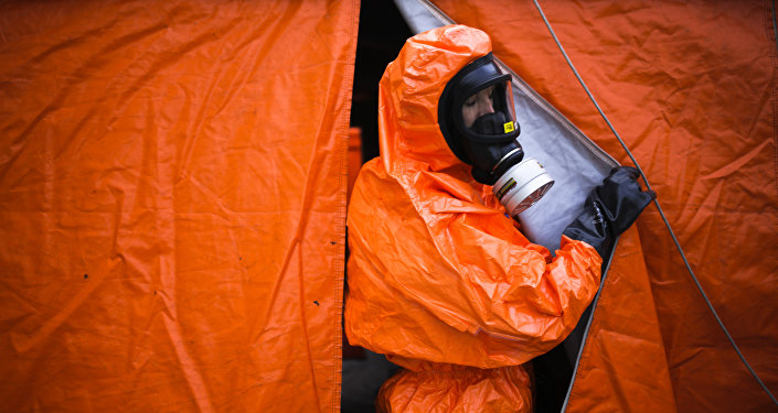 A German emergency worker looks out of a tent for decontamination during a joint anti-terror exercise of German authorities in Berlin, Wednesday, Oct. 11, 2017.