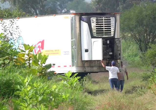 Men stand by an abandoned trailer full of bodies that has been parked in Tlajomulco de Zuniga, Jalisco, Mexico September 15, 2018 in this still image taken from a video obtained September 17, 2018.