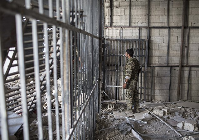A member of the U.S.-backed Syrian Democratic Forces (SDF) walks inside a prison built by Islamic State fighters at the stadium that was the site of Islamic State fighters' last stand in the city of Raqqa, Syria, Friday, Oct. 20, 2017