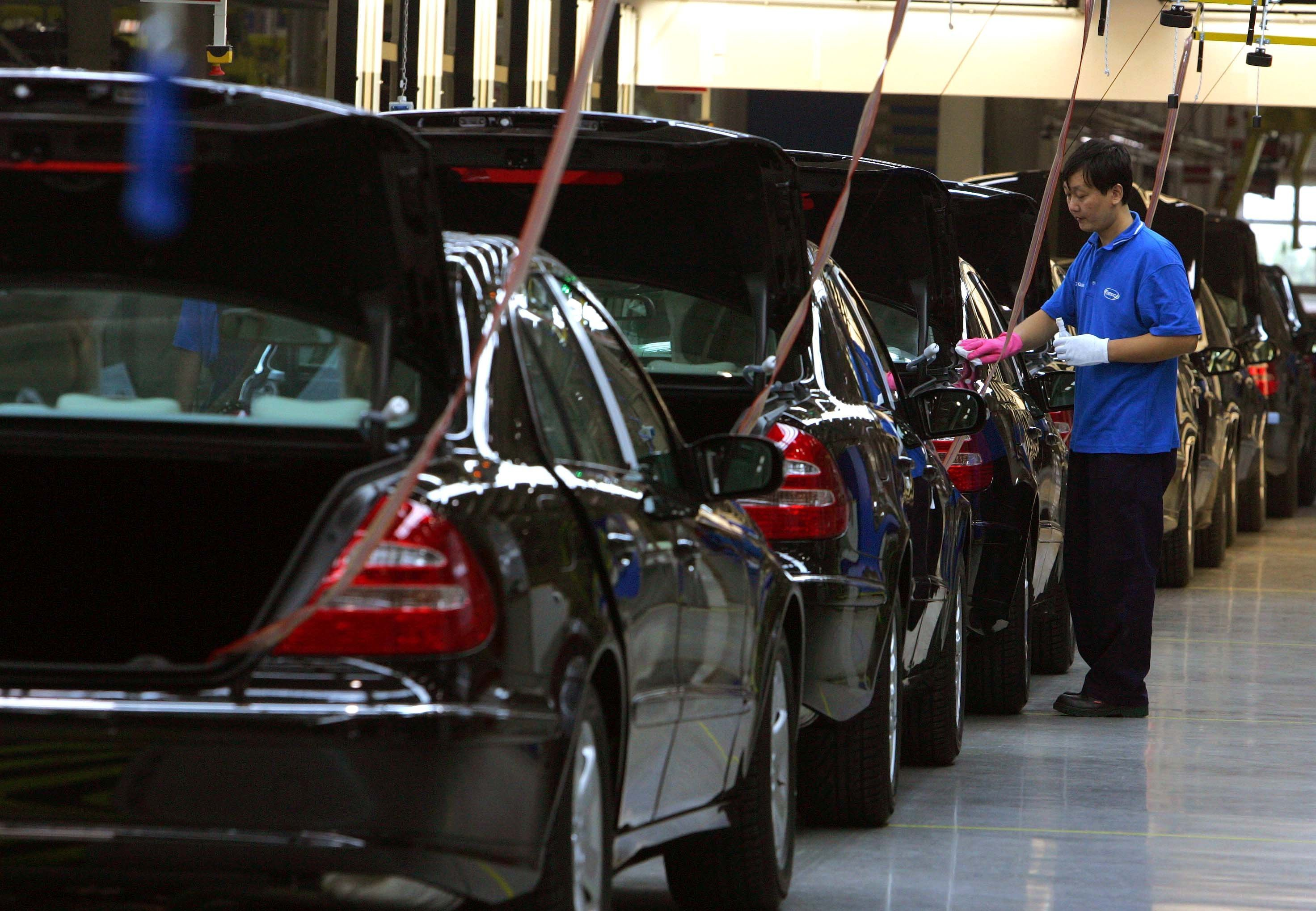 A Chinese factory worker puts final touches on the assembly line at the DaimlerChrysler factory in Beijing, China. (File)