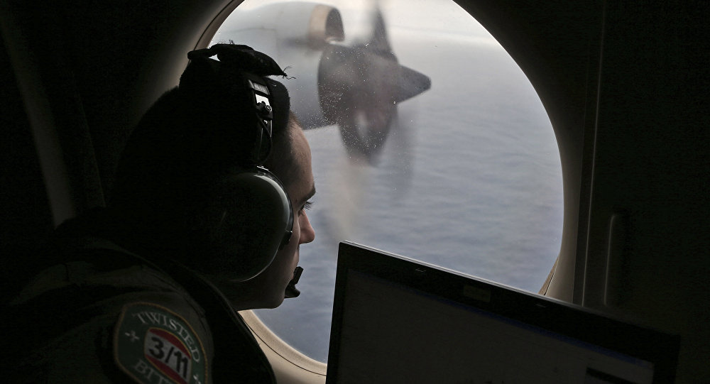 FILE - In this March 22, 2014 file photo, flight officer Rayan Gharazeddine on board a Royal Australian Air Force AP-3C Orion, searches for the missing Malaysia Airlines Flight MH370 in southern Indian Ocean, Australia