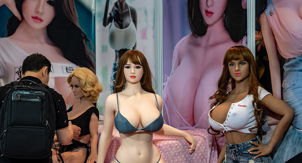 A visitor (L) checks a sex doll at a stall during the Asia Adult Expo in Hong Kong on August 29, 2018.