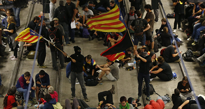 Activists advocating for Catalan secession wave Catalonian independence flags as others sit on the railway tracks at the station in Girona, Spain, Monday Oct. 1, 2018