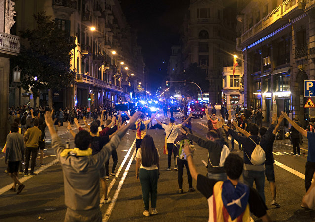 Pro-independence demonstrators stand on the middle of a street facing Catalan police officers during a protest In Barcelona, Spain, Monday, Oct. 1, 2018.
