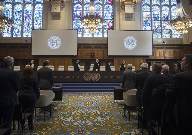 The delegations of the U.S., front left, and the Islamic Republic of Iran, front right, rise as judges, rear, enter the International Court of Justice, or World Court, in The Hague, Netherlands, Wednesday, Oct. 3, 2018, to rule on an Iranian request to order Washington to suspend sanctions against Tehran