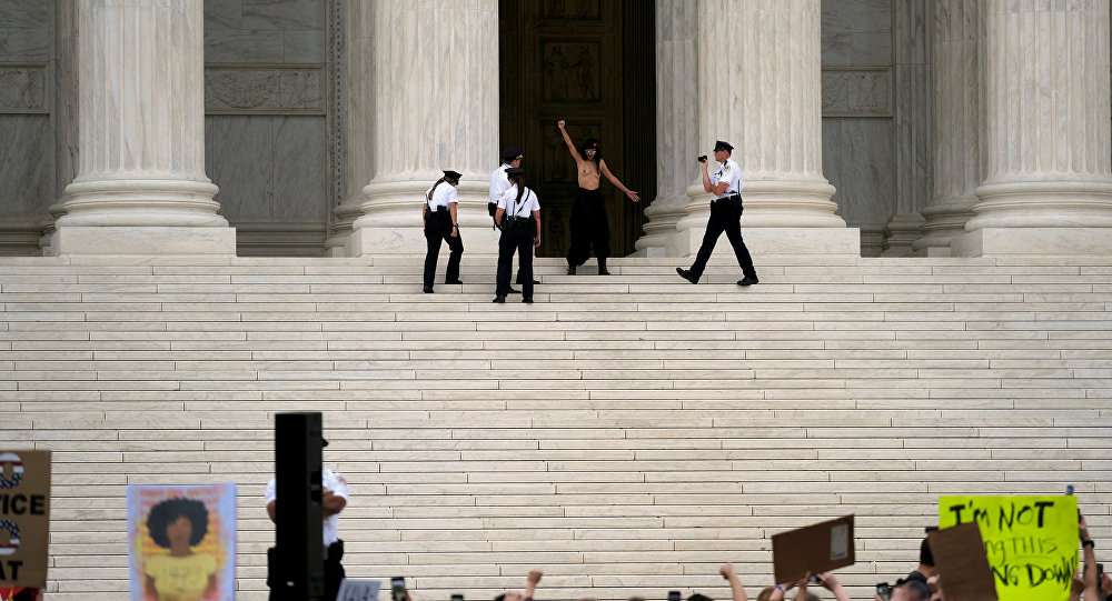 A topless woman is detained by Supreme Court Police after the Senate confirmed the nomination of Judge Brett Kavanaugh in Washington, U.S., October 6, 2018