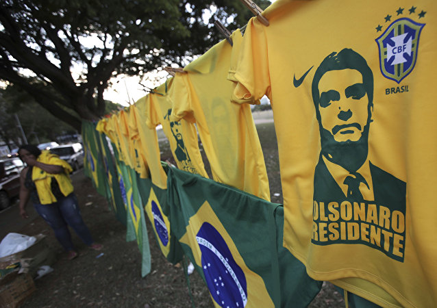 A woman sells t-shirts and flags with the image of presidential frontrunner Jair Bolsonaro in front of the headquarters of the national congress in Brasilia