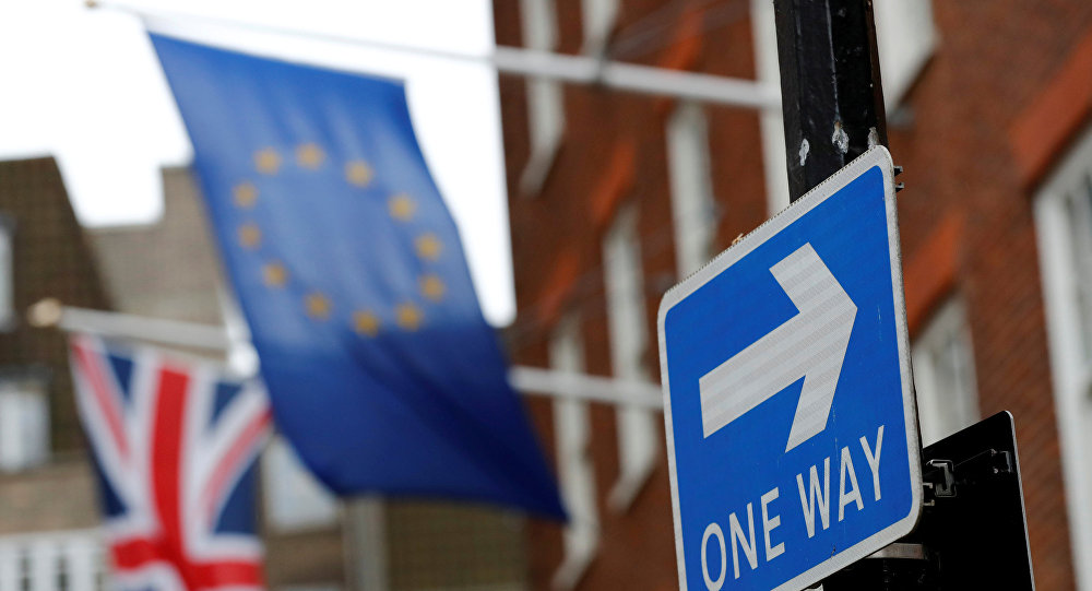 A traffic sign is seen in front of European and Union flags in London, Britain