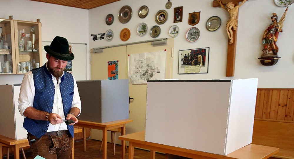 A man in traditional clothes casts his vote for the Bavarian state elections at a polling station in Maisach, Germany